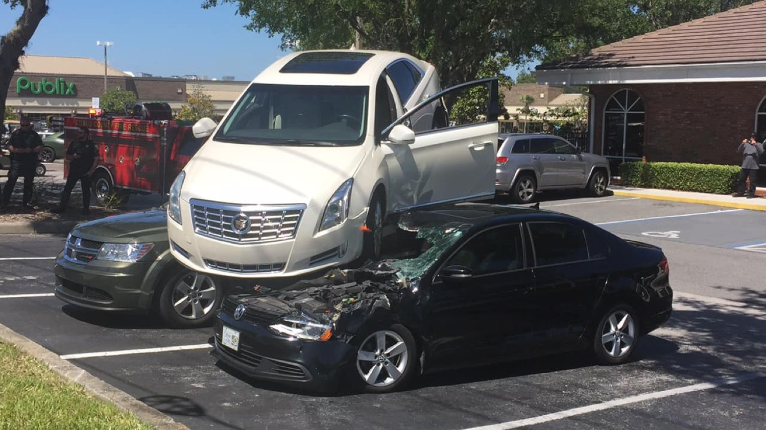 Cadillac Xts Reverses Through Intersection And Onto Parked Cars Video